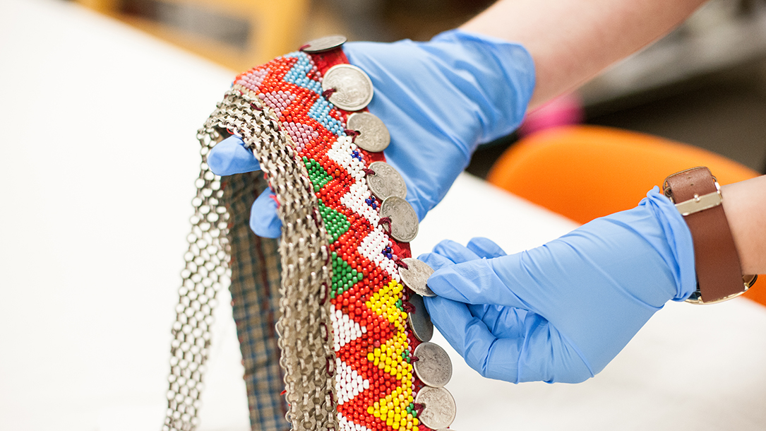 A pair of gloved hands examines an elaborate, hand-beaded necklace.