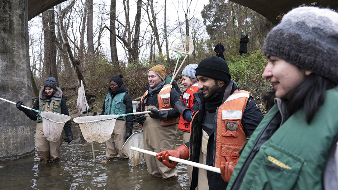 Six students stand in a river together, holding nets.
