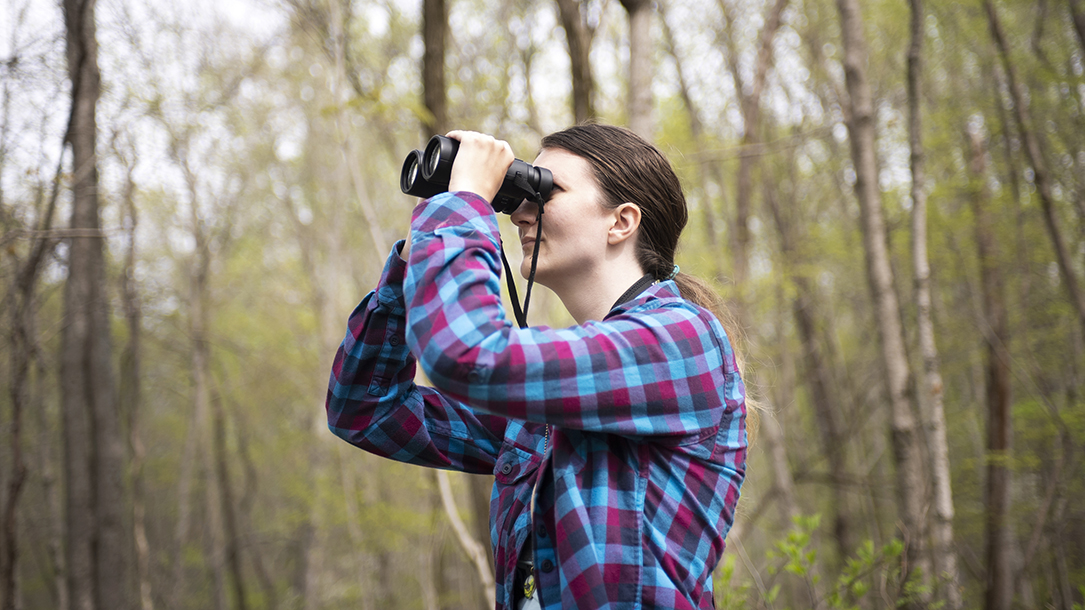 A woman looks through binoculars in the woods.
