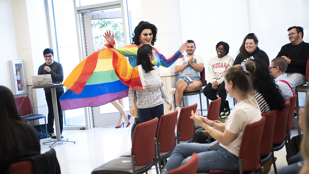 A drag queen wearing a rainbow cape smiles in front of a group of students.