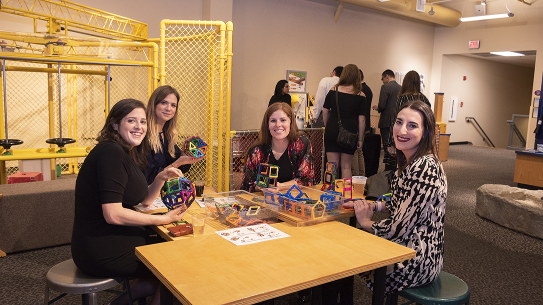 Four students play with a magnetic building toy at a children's science museum.
