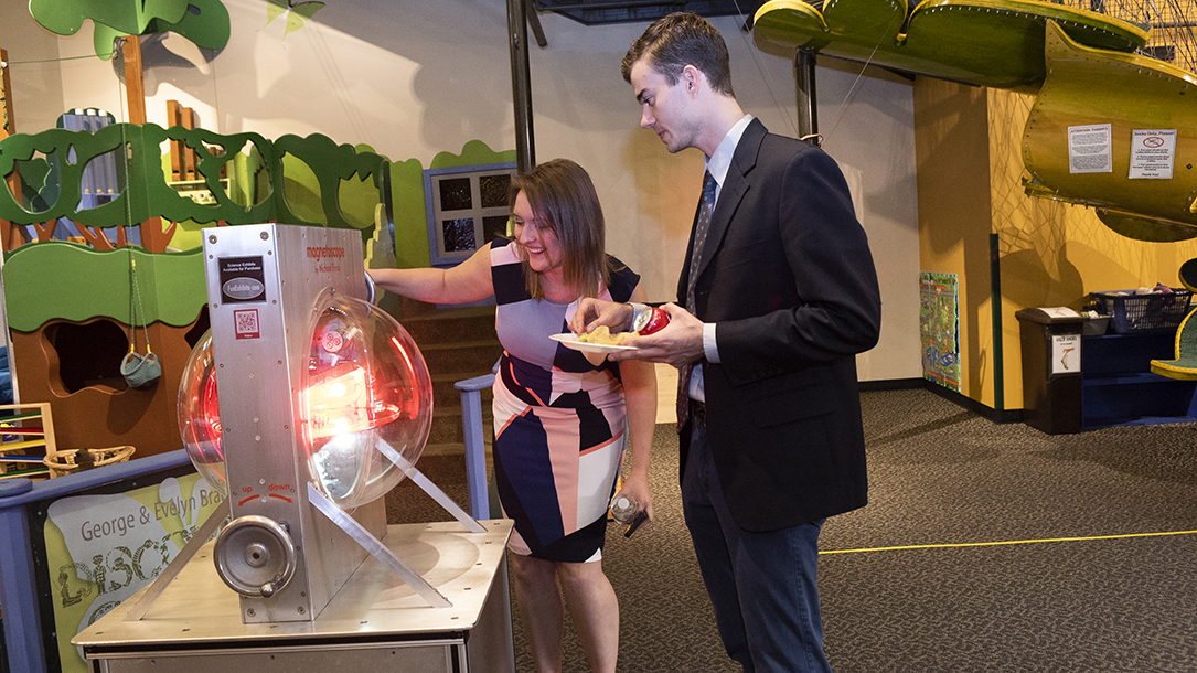 A woman and man look at a spherical display at a children's science museum.