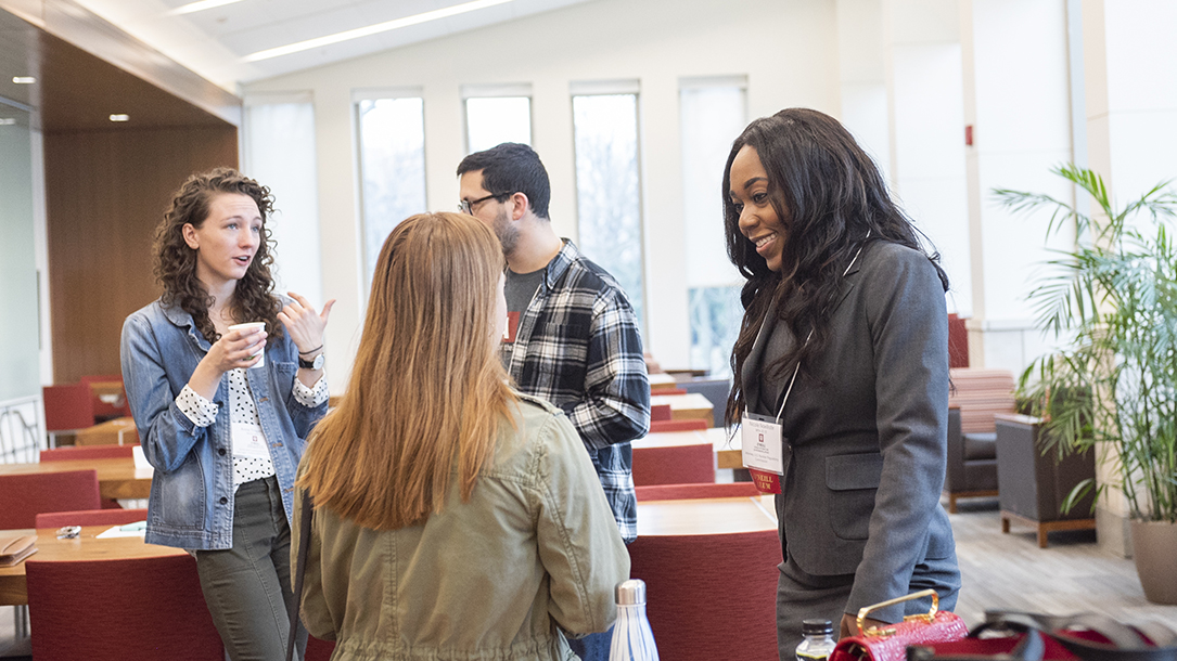 A student and an alumna of the O'Neill School of Public and Environmental Affairs speak to each other in a classroom.